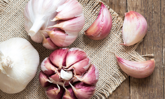 Whole and split fresh garlic on wooden background